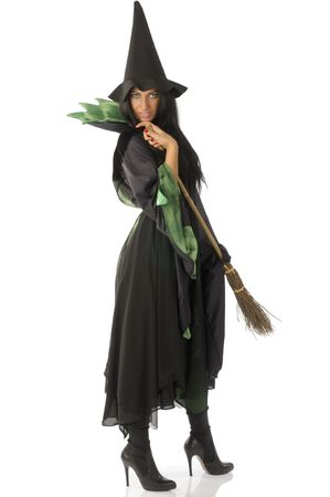 beautiful witch with hat and broom in black and green dress photo