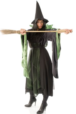 pretty witch with hat and black dress showing her broom photo