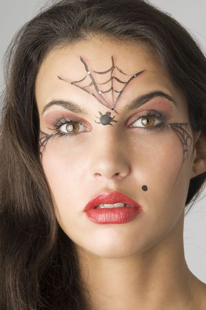 close up of young and nice brunette with spider web painted on face photo