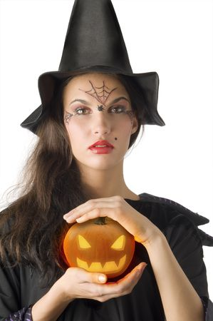 cute girl with witch hat and a little pumpkin betweeen hands photo