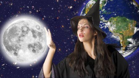strega nel cielo mantenendo la luna di distanza Archivio Fotografico