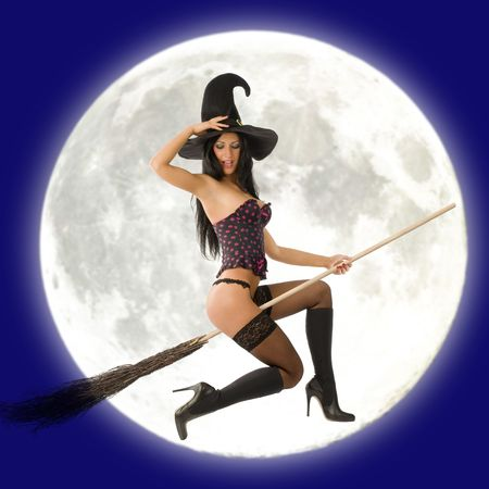 cute sexy witch in lingerie flying with broom and a big moon behind Stock Photo