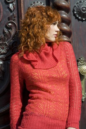 close up of a young and beautiful woman with red pullover near old door photo