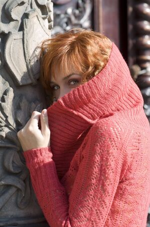 red haired woman hidding herself behind her red pollover near old building photo
