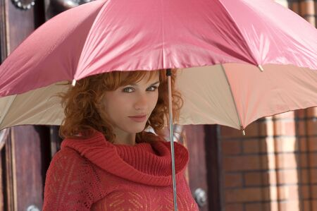 nice girl under a red umbrella in a sundlay day photo