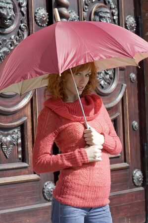 cute red-haired girl near old fashion door with red umbrella under the sun photo