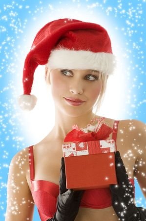 close up of young beautiful blond santa claus with red christmas gift box photo