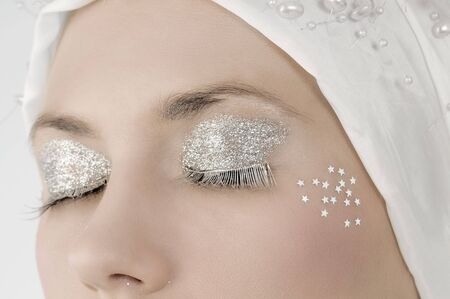 magic eye: desaturated close up on eyes with silver make up and silver eyelashes
