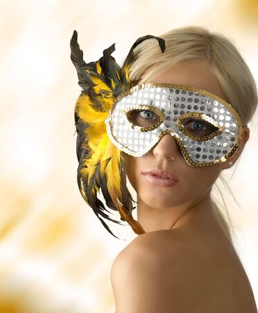 beautiful blond girl with glitter silver mask and yellow feather photo