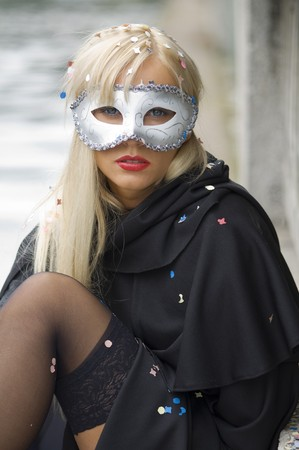 blond girl near river with white carnival mask and black cloak photo