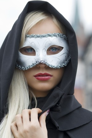 pretty blond hidding her face with white mask and black hood photo