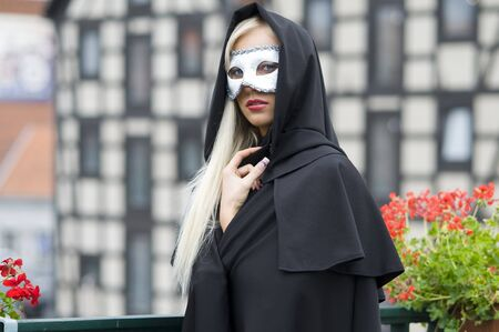 outside portrait of cute blond with white mask and black cloak with hood