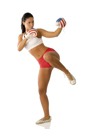 cute brunette with boxing gloves starting to kick Stock Photo