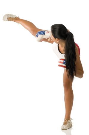 cute brunette with boxing gloves giving an high kick photo