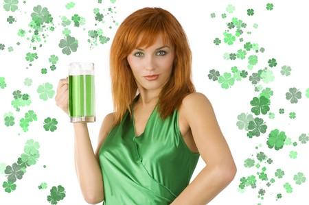 lass: redhead Irish Lass posing in green dress with glass of green beer Stock Photo
