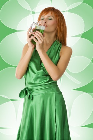 red head girl: graceful red head girl in act to drink green beer with pleasure