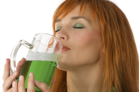 close up of pretty redhead girl drinking green beer as usual in saint patrick day photo