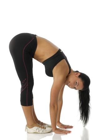 strecthing: pretty girl strecthing her body making gymnastic in gym dress