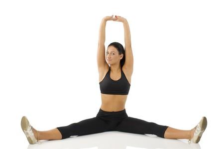gambe aperte: bella ragazza seduta strecthing il suo corpo con il braccio e le gambe aperte