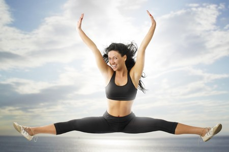 strecthing: nice girl in black sportwear jumping with wind in hair