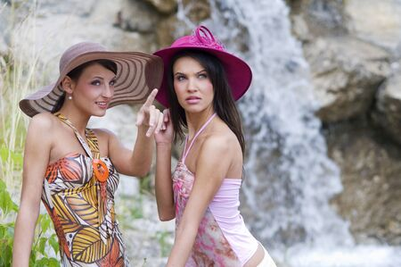 two pretty women in colored dress and hat standing and chatting near a waterfall photo