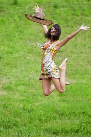 young athletic woman in colored dress and straw hat jumping in the field photo