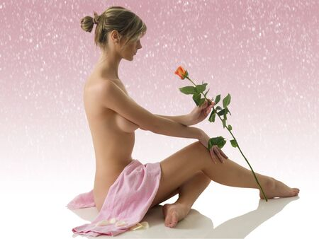 beautiful nude woman sitting on white with a pink towel and a rose