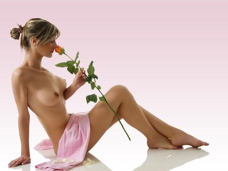 mujer desnuda sentada: hermosa mujer desnuda sentada en blanco con una toalla de color rosa y oler una rosa Foto de archivo