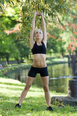 gym dress: blond girl in fitness dress making gym exercise outdoor in park Stock Photo