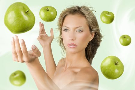 blond pretty girl trying to catch some green apple flying all around her Stock Photo - 4516075