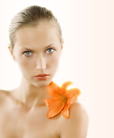 great portrait of a blond girl with wet hair and an orange lily on her shoulder Stock Photo - 4516077