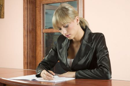 blond girl in front desk of hotel reception writing on a book photo