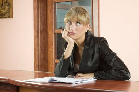 blond girl at  front desk of Hotel reception lost in thought photo