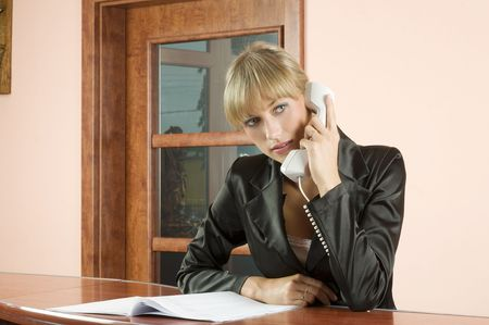 blond girl in Hotel reception talking at telephone photo