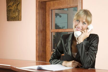cute blond woman at front desk smiling and talking at phone photo