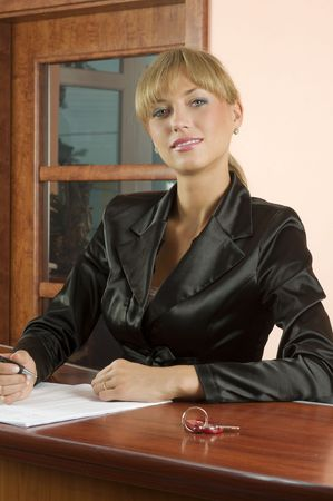 blond girl front desk of hotel reception in formal black suit photo