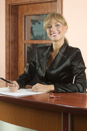 blond girl Hotel reception in black suit smiling photo