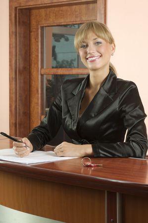 blond meisje receptie in zwart pak glimlachende Stockfoto