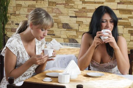 two friends having a good time in a cafe drinking a cup of tea photo