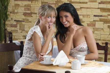 giggle: two friends in a cafe looking in camera and smiling Stock Photo