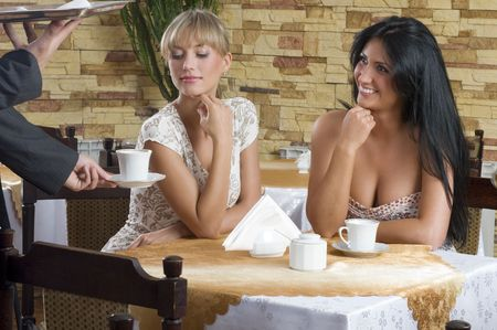 two friends waiting for the waiter taking cup of tea photo