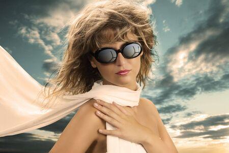 sole occhiali: ragazza bionda con una sciarpa di seta e occhiali da sole in un ritratto d'epoca LANG_EVOIMAGES