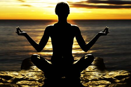 silhouette of woman on rock in the sunset sea in a classic yoga pose