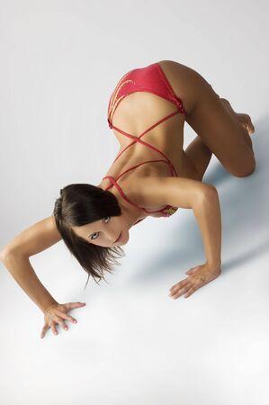 ass standing: sexy brunette in swimwear taking body builder pose