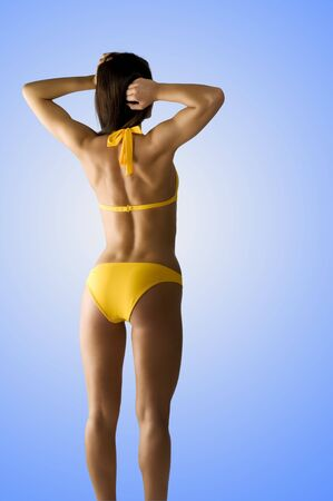 brunetta in yellow bikini showing her back side fitness body photo