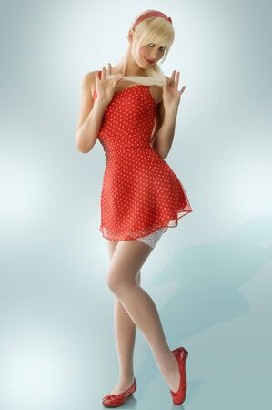 pretty blond pin up in red dress and white stockings taking pose photo