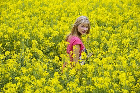 Happy blond girl with pink t-shirt in a yellow field Stock Photo - 4941538