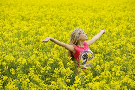 happy blond girl with open arms in a yellow field smiling Stock Photo - 4941550