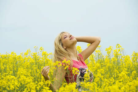 cute blond girl in yellow field smiling at the sky Stock Photo - 4941549