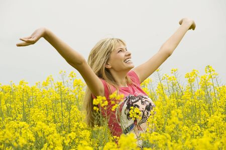 happy blond girl with open arms enjoying and smiling at the sky Stock Photo - 4941540